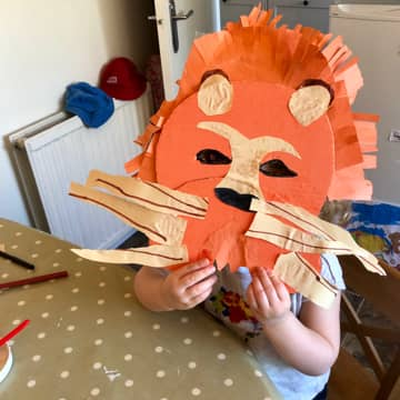 A lion mask made out of the orange KIDLY box and yellow tissue paper